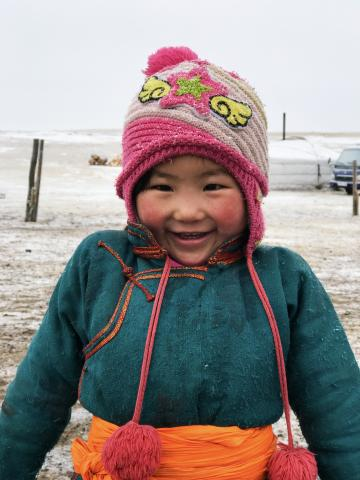 4 year old Batjargal Margadmaa smiles outside her home where she lives in a temporary yurt with her mother and father, and two younger brothers.