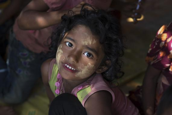 A girl smiles for the camera while attending class in a UNICEF-supported learning centre in Camp 7 of Balukhali refugee camp in Cox's Bazar, Bangladesh